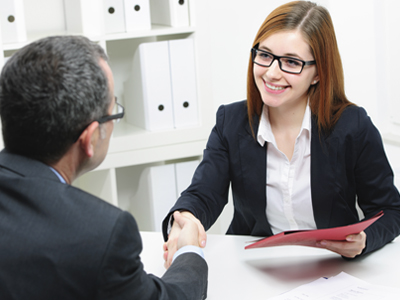 A man and woman shaking hands during a business meeting