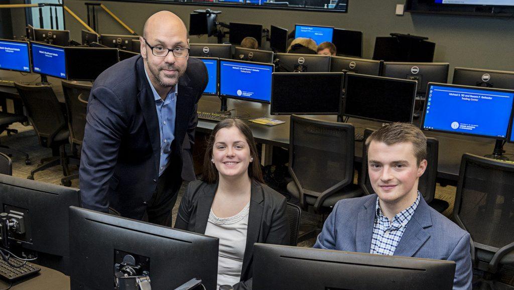 BHIC members Ryan O'Donnell and Anna Perrotta analyze stock picks with club advisor Richard Jakotowicz.