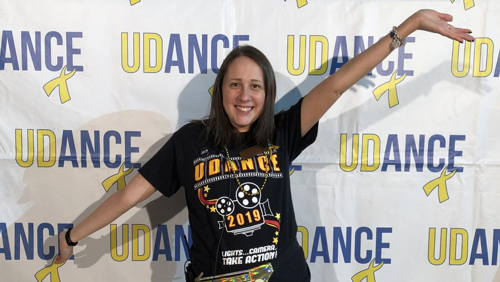 Allison Worms poses for a photo in front of a UDance background