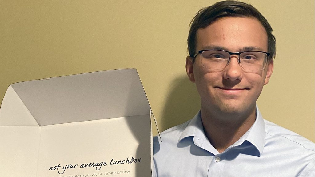 Eric Albiez poses for a photo with a box from his internship.