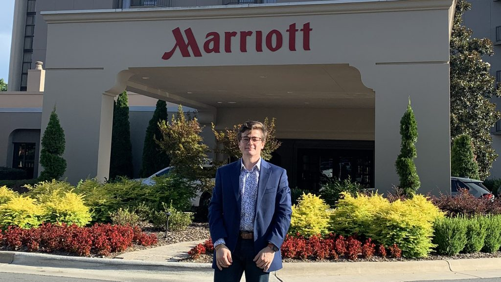Gabe Castro poses outside of a Marriott Hotel for a photo