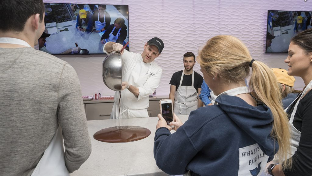 Vita Nova Executive Chef John Deflieze tempers chocolate, an essential step for making smooth, glossy chocolate, while All You Knead is Love Club President Evan Greif and fellow members look on.