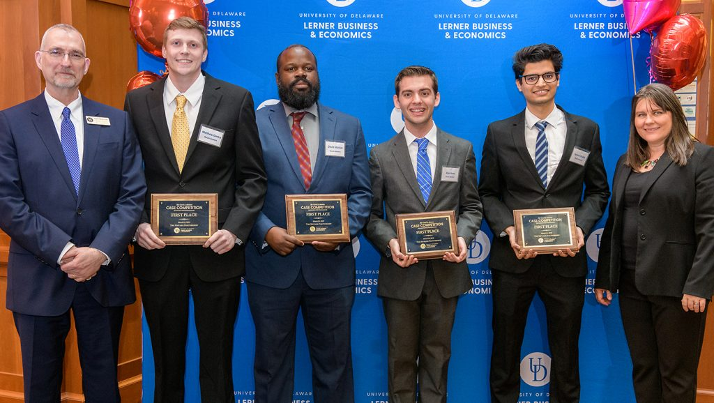 Matthew Gentry, Alex Huey, David Mahon and Apruva Shukla smile after the announcement that their team, the Buzzer Beaters, had won the 2019 Carol A. Ammon Case Competition.