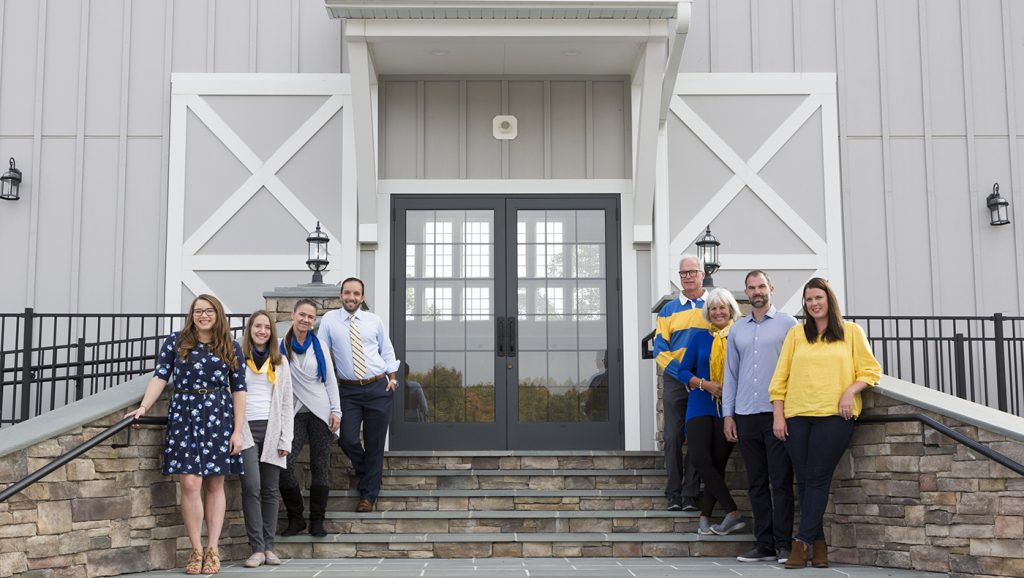 Blue Hens working on Rosewood Farms pose for a photo in front of one of their buildings.
