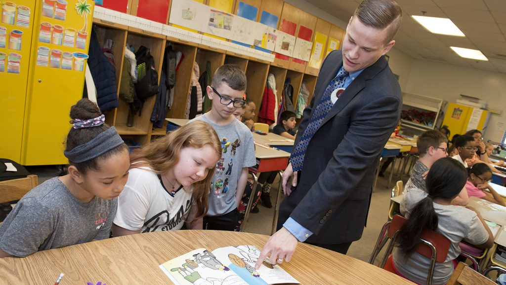Lerner alumnus Everet Zicarelli teaches a lesson in personal finance to fourth graders Aliyah Jackson, Kayla Otto and Shane Bradley at Thurgood Marshall Elementary School for Teach Children to Save Day Week.