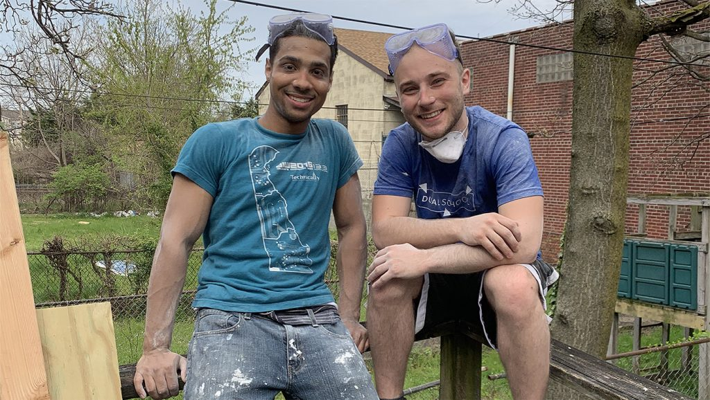 Two students pose outside of a house they are constructing.